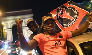 Paris Saint-Germain supporters wave flags as they celebrate on the Champs Élysées after their team's 3-0 win over RB Leipzig.