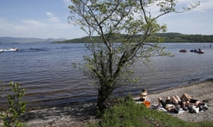Friends and families sunbathe at Duck Bay, in the Loch Lomond and the Trossachs National Park