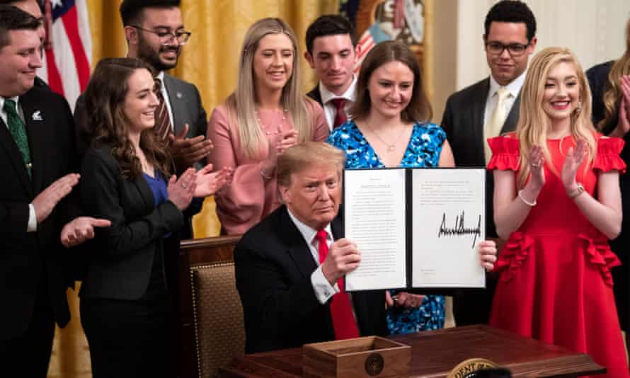Donald Trump holds up a copy of an executive order on 'improving free inquiry, transparency, and accountability on campus' during a signing ceremony at the White House.