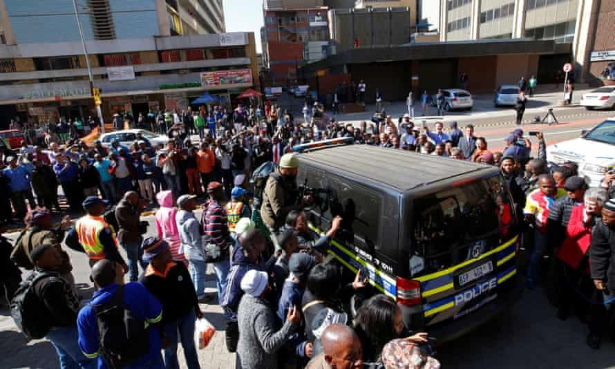 Journalists crowd around a van believed to be carrying Pistorius after his sentencing.
