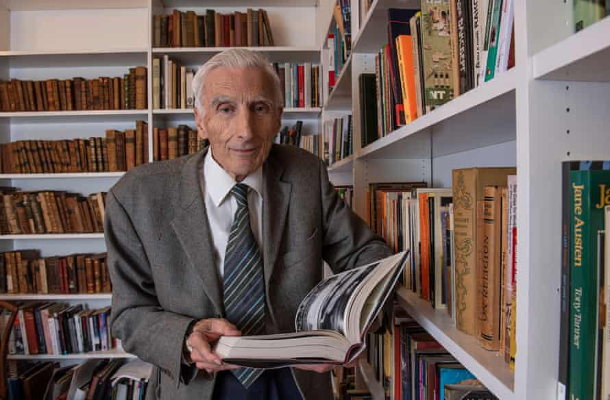 martin rees standing by his bookshelves holding an open book