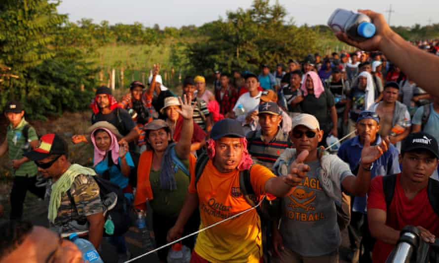 Migrants receive supplies while walking by the road that links Ciudad Hidalgo with Tapachula, Mexico on 2 November.