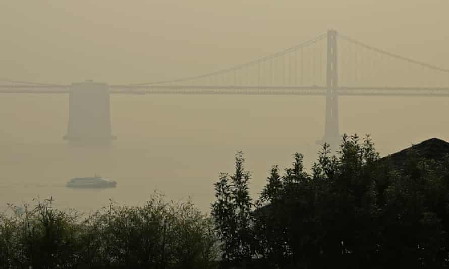 A ferryboat and the San Francisco-Oakland Bay Bridge are obscured due to smoke and haze from wildfires.