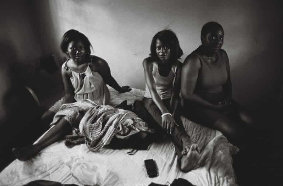 Mavis sits on a bed alongside two young girls