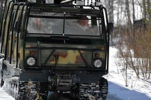 Vladimir Putin pilots an all-terrain vehicle through thick woodland.