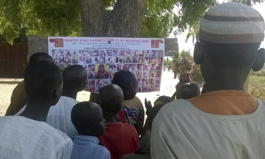 People gather on the streets of Maiduguri to look at the list of Boko Haram men wanted by the Nigerian military.