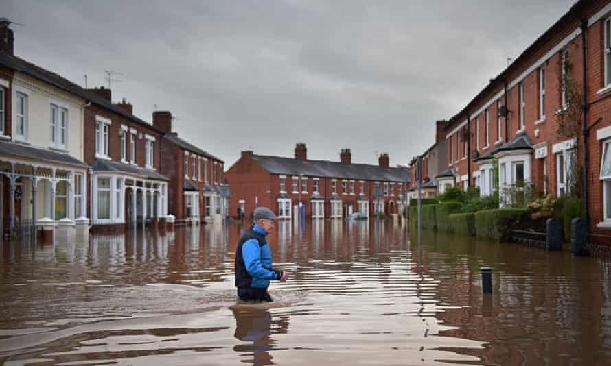 A man makes his way through flood water in Carlisle.
