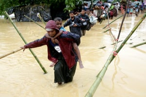 Rohingya refugees walk on a bamboo made bridge to cross a small canal as they move from their temporary camp due to rain ruining most of their makeshift tents, near Kutupalong, Ukhiya, Bangladesh