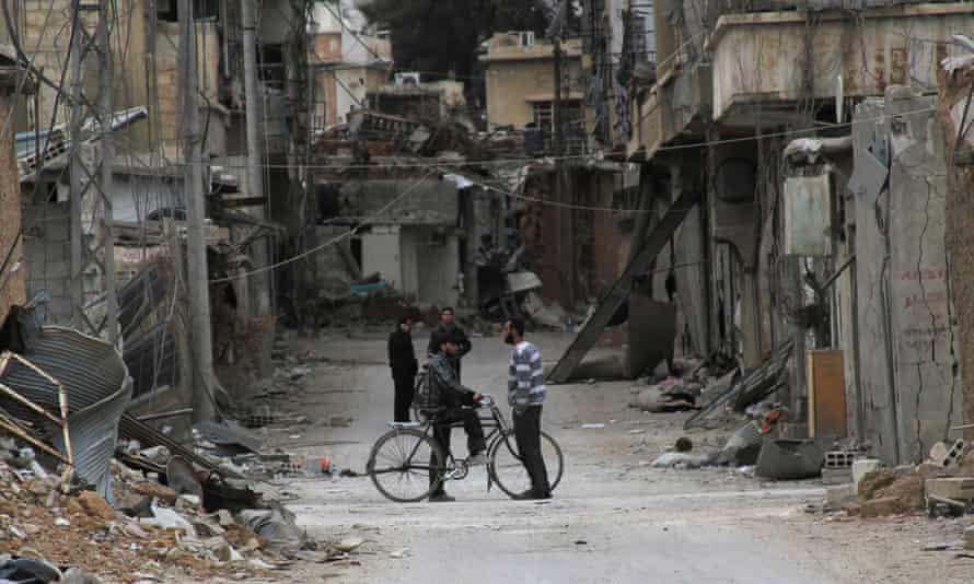Men chat near damaged buildings in Daraya, near Damascus, in 2014
