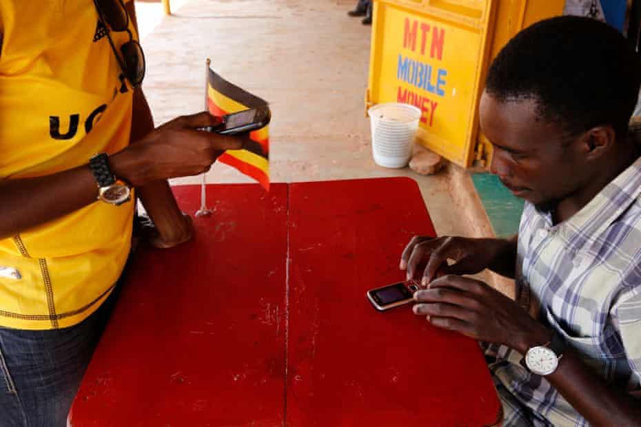 Ugandan woman sending money by smartphone.