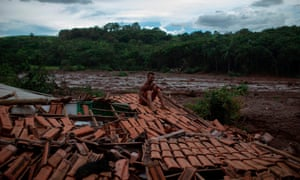 A man sits on the roof of his home to protect what is left of his family's belongings.