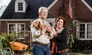 Ron Kasting holding a dog, and Ann Ladenberger, standing together in front of their home