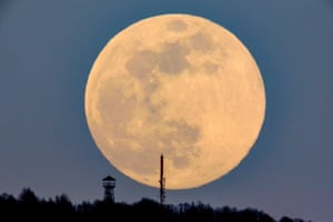 A lookout tower and the broadcast tower of Antenna Hungaria at the top of Karancs mountain are seen against the rising moon at Karancskeszi village, Hungary