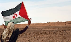 A Sahrawi girl flies the flag of Western Sahara in front of the Moroccan Wall, a 2,700 km-long structure mostly consisting of a sand wall or berm.