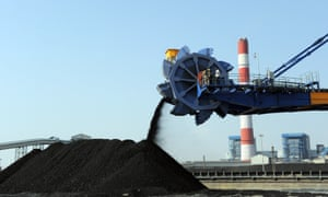 workers use heavy machinery to sift through coal at an Adani Power company thermal power plant