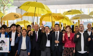 Chu Yiu-ming (4th L), law professor Benny Tai (C) and sociology professor Chan Kin-man (3rd R) and other pro-democracy campaigners chant before entering the West Kowloon Magistrates Court in Hong Kong