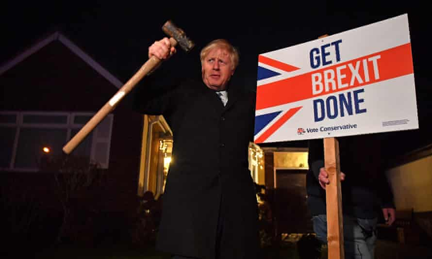 "Boris Johnson poses after hammering a ""Get Brexit Done"" sign into the garden of a supporter"