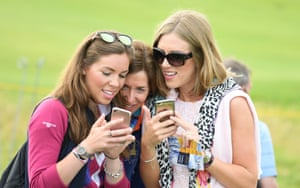 Fans check their mobile phones as they watch a practice round ahead of the Open Championship at Royal Portrush Golf Club
