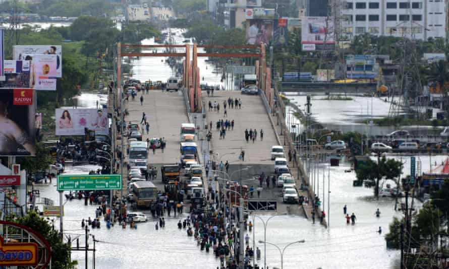 Indian residents and motorists gather on a flyover as others wade through floodwaters in Chennai.