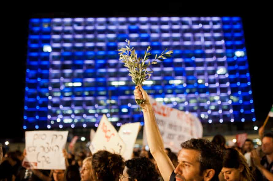 A protest in Rabin Square in central Tel Aviv calling for the end of the war in Gaza. In the background, city hall is lit to represent the Israeli flag.