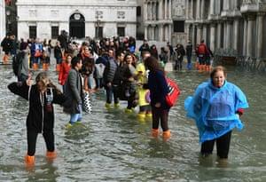 Tourists wade through water