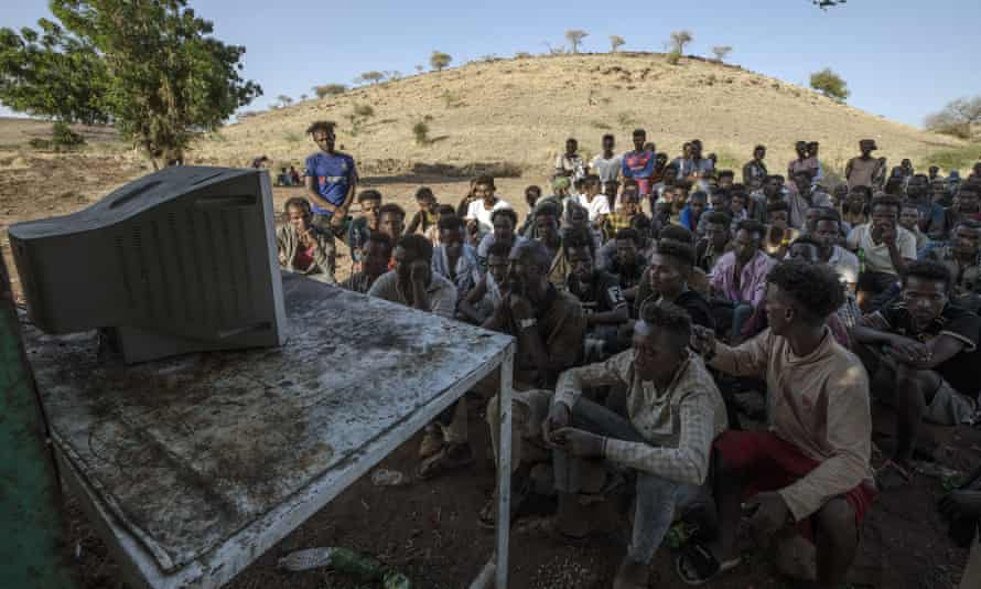 Men who fled the conflict in Tigray watch the TV news at Umm Rakouba refugee camp in Qadarif, eastern Sudan