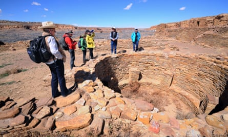 A guide talks to visitors beside an excavated kiva in the ruins of a massive stone complex (Pueblo Bonito) at Chaco Culture National Historical Park.