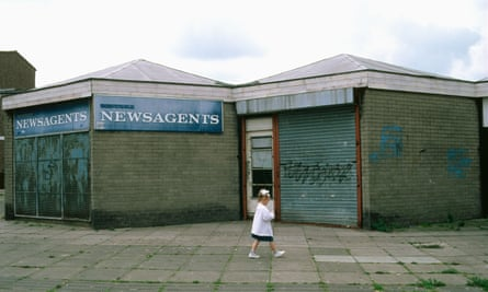 A small girl walks past a closed-down shop on an estate in Skelmersdale, Lancashire