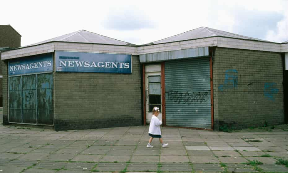 Small girl walking past boarded up shops on run down estate Skelmersdale