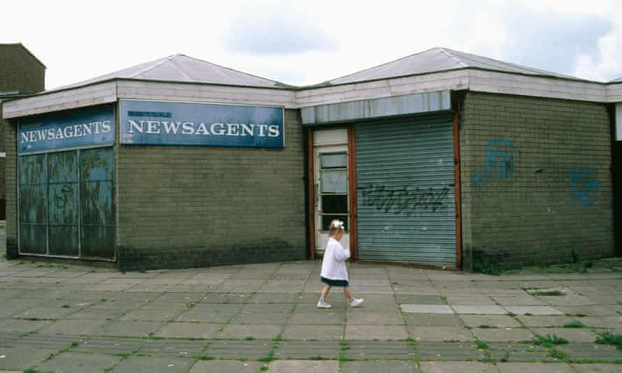 Small girl walking past boarded up shops on run down estate