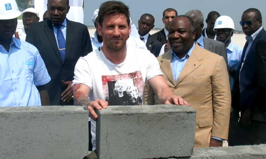 Lionel Messi lays the first stone at the construction site of a football stadium in Port-Gentil, Gabon, with the country's president, Ali Bongo, to his left.