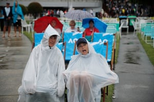 Tennis fans wait for play to resume as it rains on the first day of the tournament