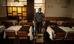 سیندو گونزالس قبل از ورود محدودیت های جدید در بارسلونا ، محصولات را قبل از ظهر آخرین روز افتتاحیه رستوران Envalira حمل می کند.