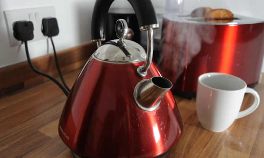 Kettle boiling with steam and a toaster cooking toast behind it in a kitchen