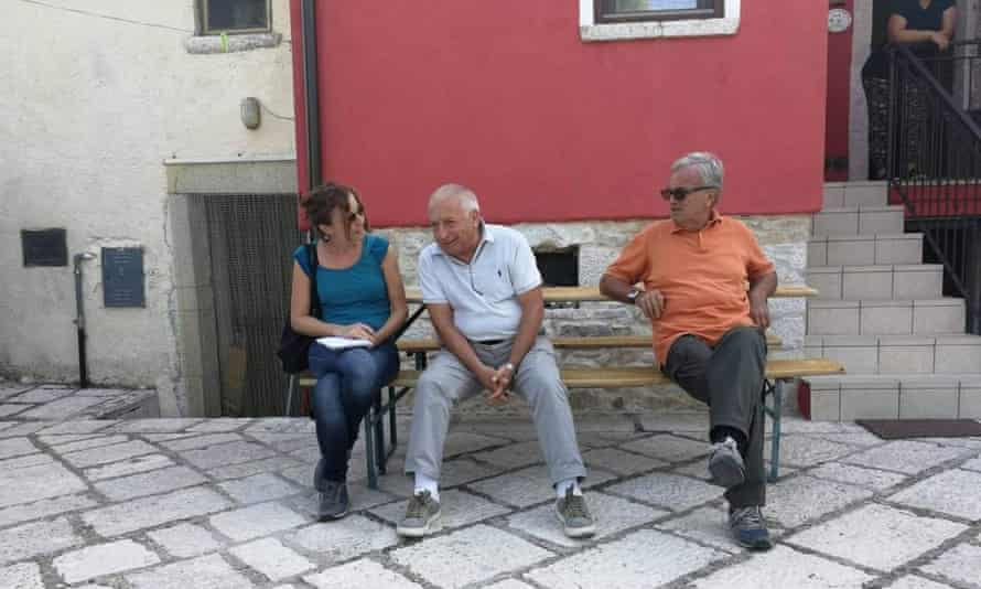 A woman sitting on a bench in a piazza talking to two older men