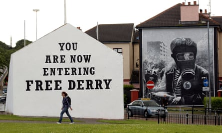 The mural on the right, depicting a boy clutching a petrol bomb was painted by Tom Kelly in the 1990s as one of a series of 12 murals telling the story of Bloody Sunday.