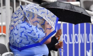 A spectator drinks champagne under an umbrella as ran delays the start of the first day of the second Ashes Test at Lord's.