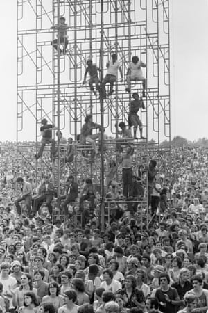Members of the audience climb the sound tower to secure a better view at the Woodstock Music & Art Fair, Bethel, NY, August 15, 1969.