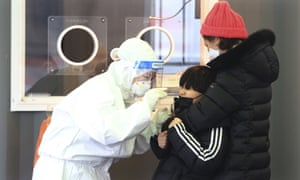 A medical worker takes a nasal sample from a boy during Covid-19 testing at a coronavirus testing site in Seoul.
