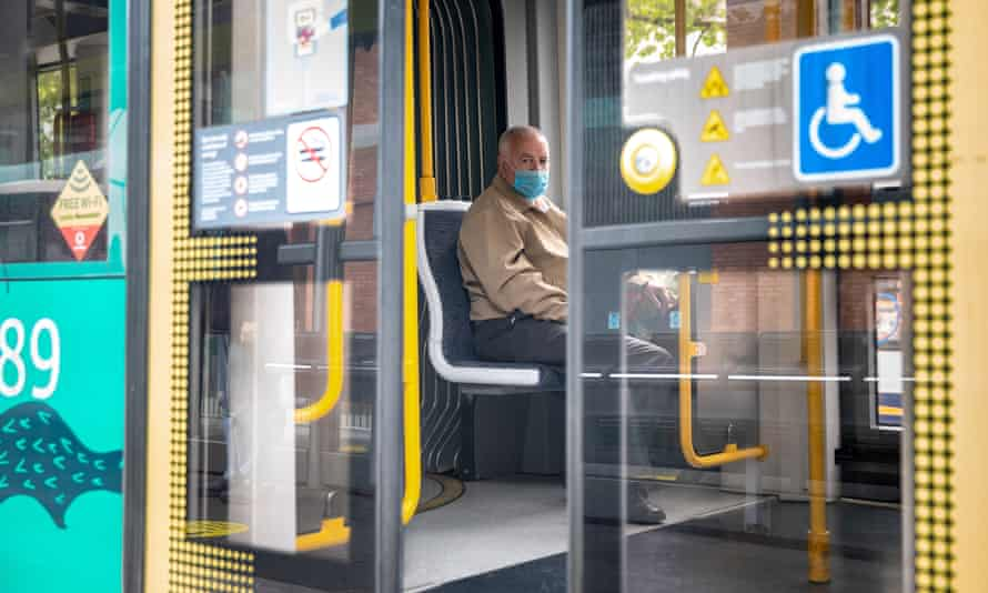 A man wearing a mask looks through closing doors of a tram at Piccadilly Gardens in Manchester.