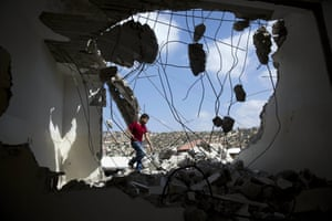 A Palestinian youth walks through the rubble of the demolished house of Bilal Abu Zeid