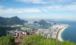 Visitors take in the view of the Rio skyline after a hike to the top of Dois Irmaos Mountain.