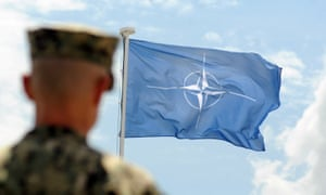 A soldier stands with his back to camera in front of a Nato flag