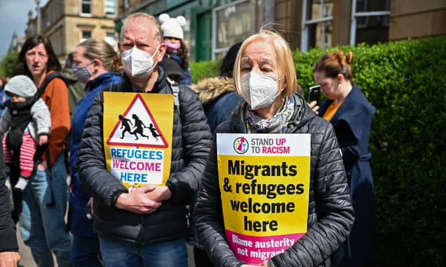 Protesters hold up signs as they block an immigration control van, preventing it from leaving Kenmure Street in Glasgow.