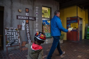 """A voter and his son walk past a polling sign and a """"No Border Wall"""" display at the Sherman Heights Community Center, a polling place for the presidential primary during Super Tuesday on March 3, 2020 in San Diego, California."""