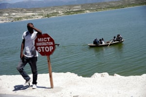 A man leans on a sign as a group of people sail in a rowboat at the border of Malpasse, Haiti.