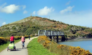 Cyclists approaching the disused iron railway bridge on the Camel Trail in Cornwall