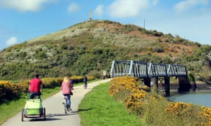 Cyclists approaching the disused iron railway bridge on the Camel Trail in Cornwall.