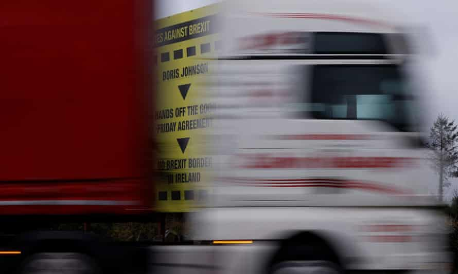 A lorry passes a Brexit themed poster on the road close to the border between Northern Ireland and Ireland near Newry.