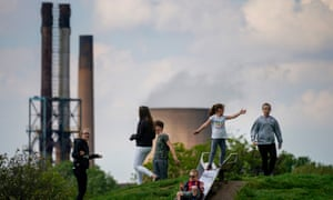 Children play against the backdrop of British Steel's Scunthorpe works which has been forced into liquidation